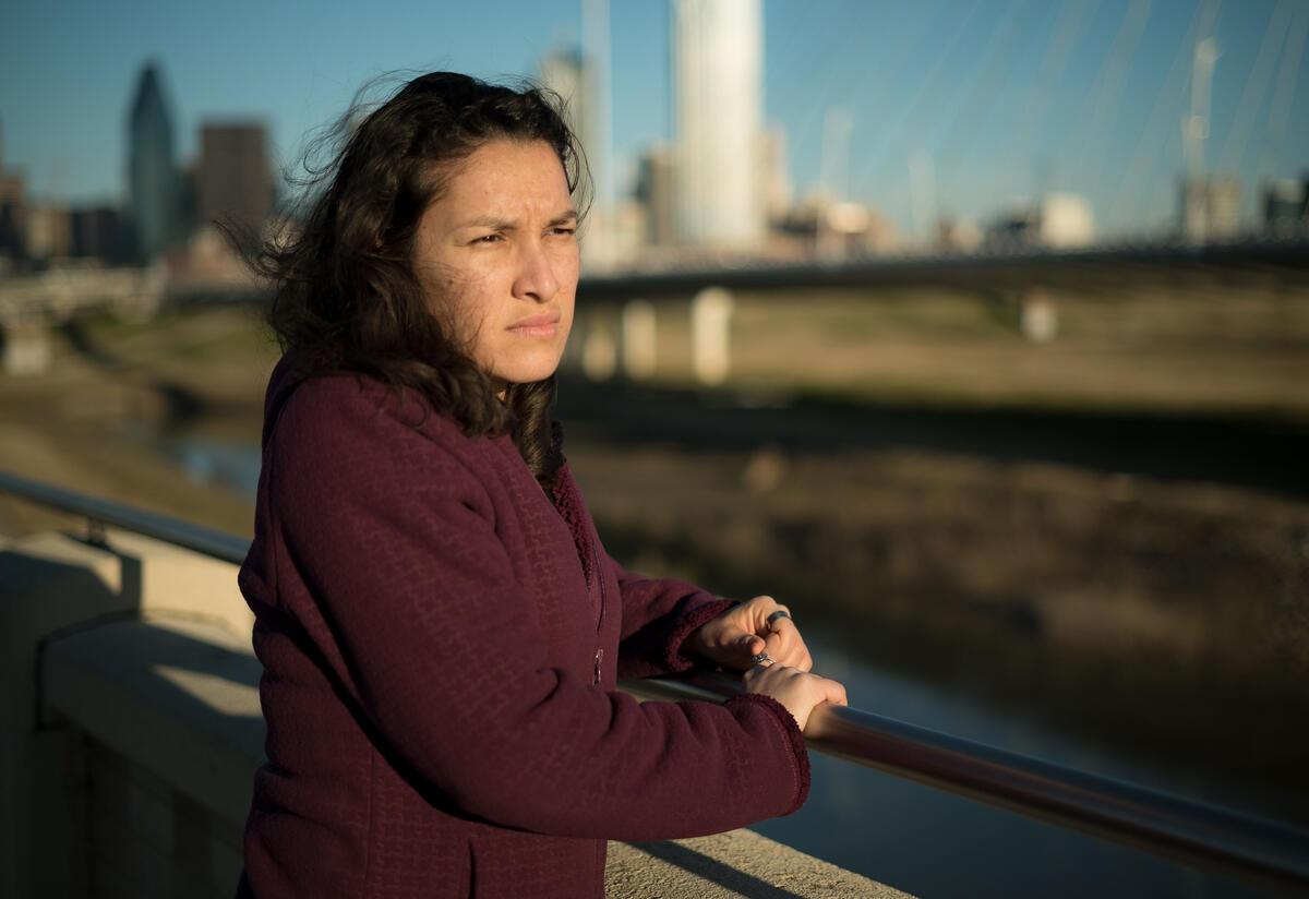 Valentina, una refugiada de El Salvador, se encuentra en un puente en Dallas, TX, y mira hacia el agua.