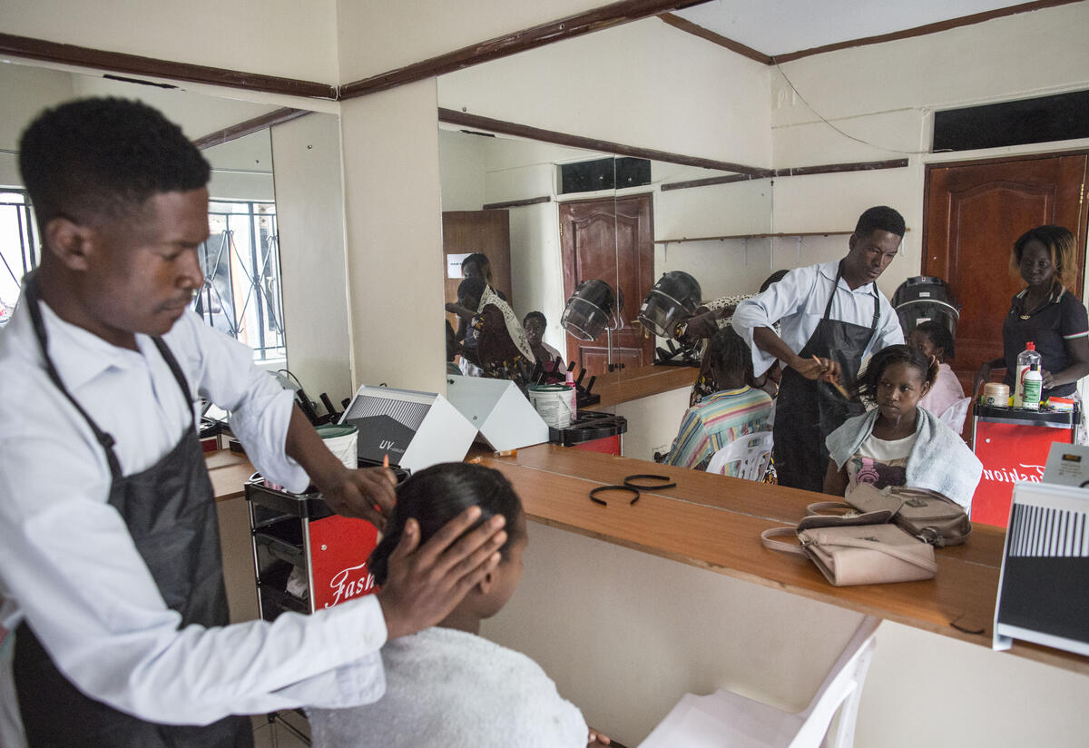 A man styles a seated woman's hair in front of a large mirror during a hairdressing training class.