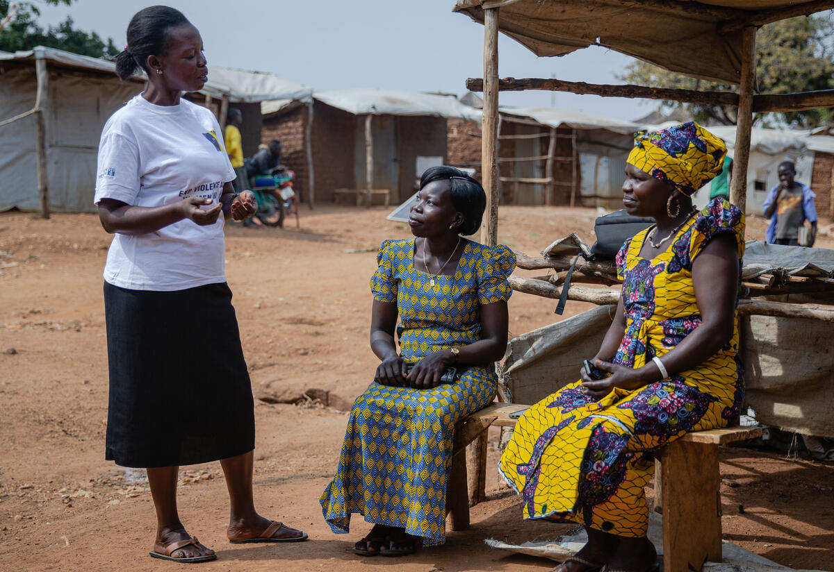 Three women talk to one another in a refugee camp, two sitting down and the other standing.