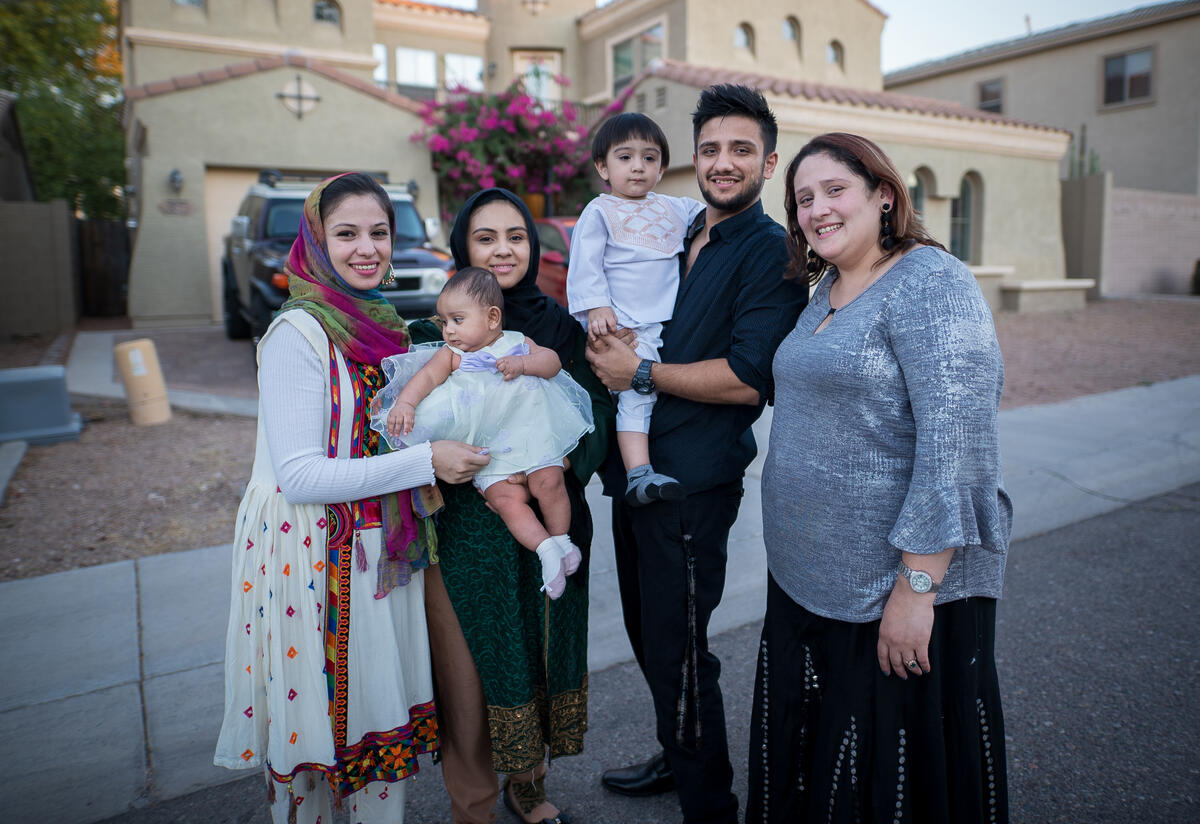 In front of a house, Muska Haseeb holds a baby and poses with her family, one man, two other woman and two babies.
