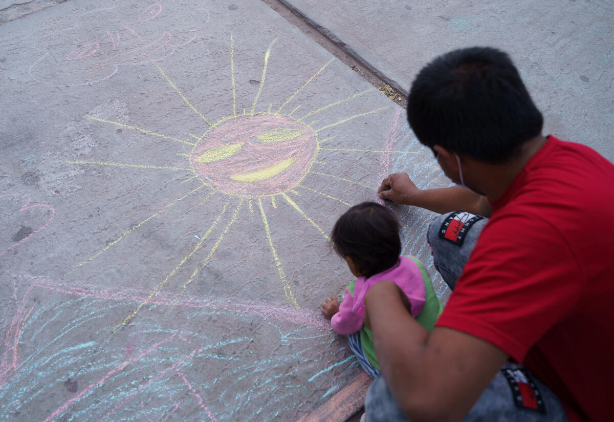 A father and young child bend over the ground drawing with chalk. They have already drawn a large sun.