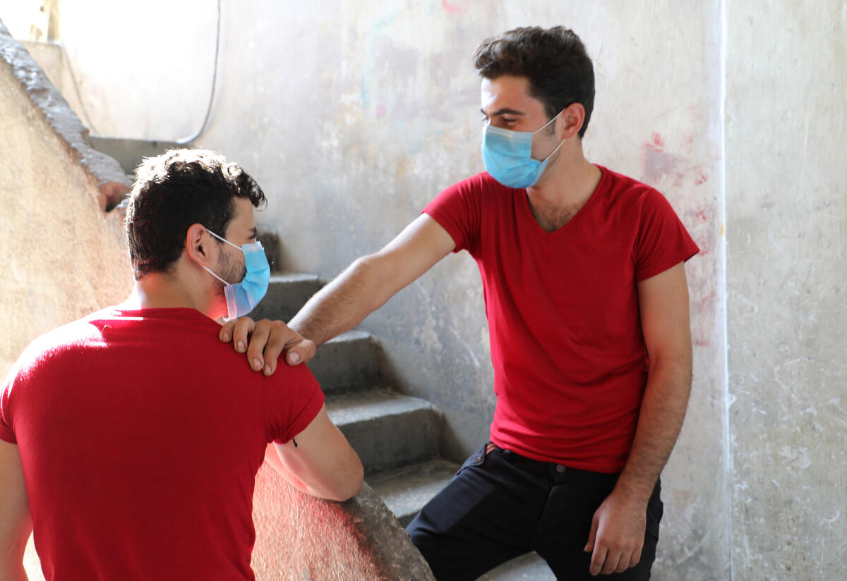 21-year-old Barakat, a Syrian refugee in Lebanon, stands on a stair wearing a mask with his hand on the shoulder of his brother Mohammed. They are wearing matching shirts.