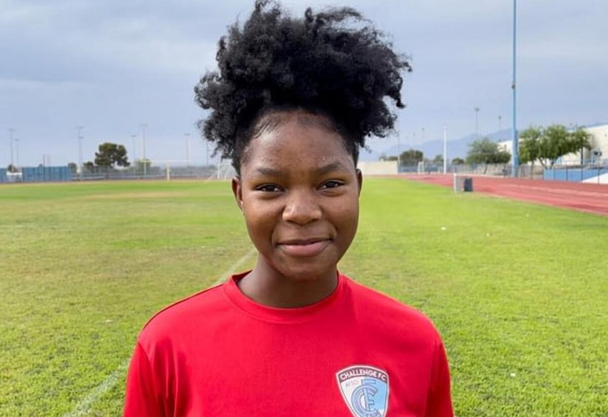 Wearing a red shirt and smiling, Kezia looks at the camera while on a soccer field