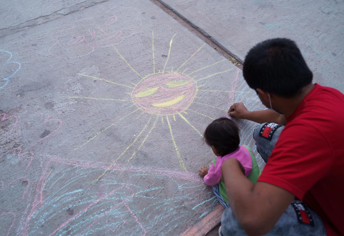 Un padre y su hijo dibujan con tiza.