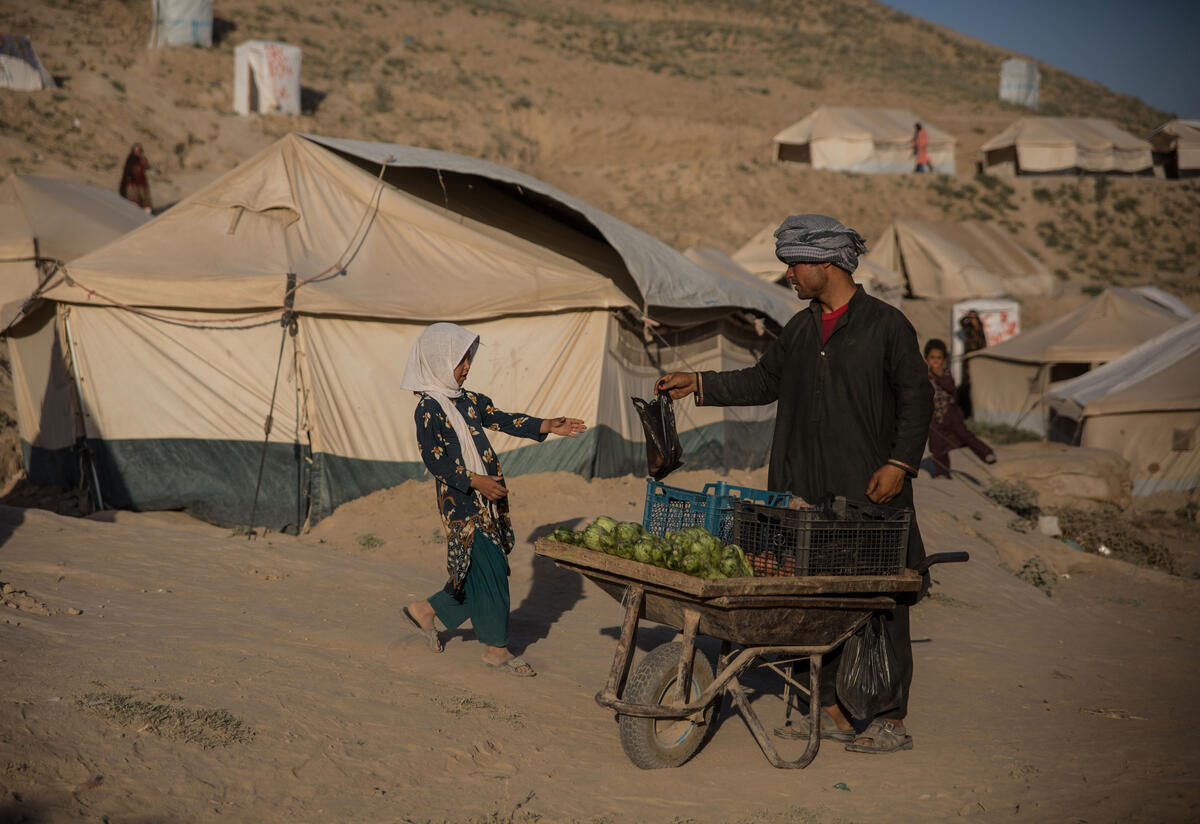 With tents in the background, a man with a fruit cart hands a bag to a young girl.
