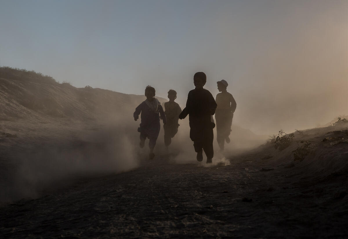 Children run through a desert and mountain landscape. The light is such that their faces are obscured.