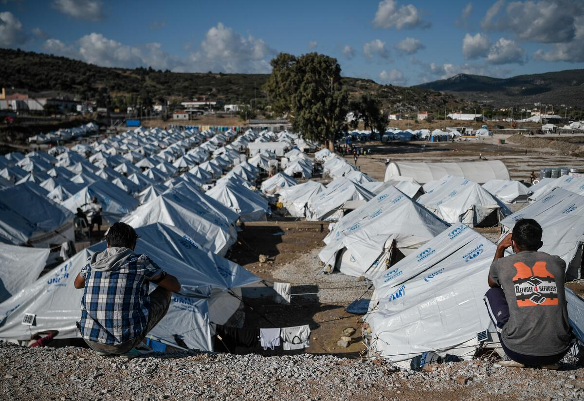 Two refugees sit looking out over a sea of white tents in a refugee camp on Lesbos, Greece.