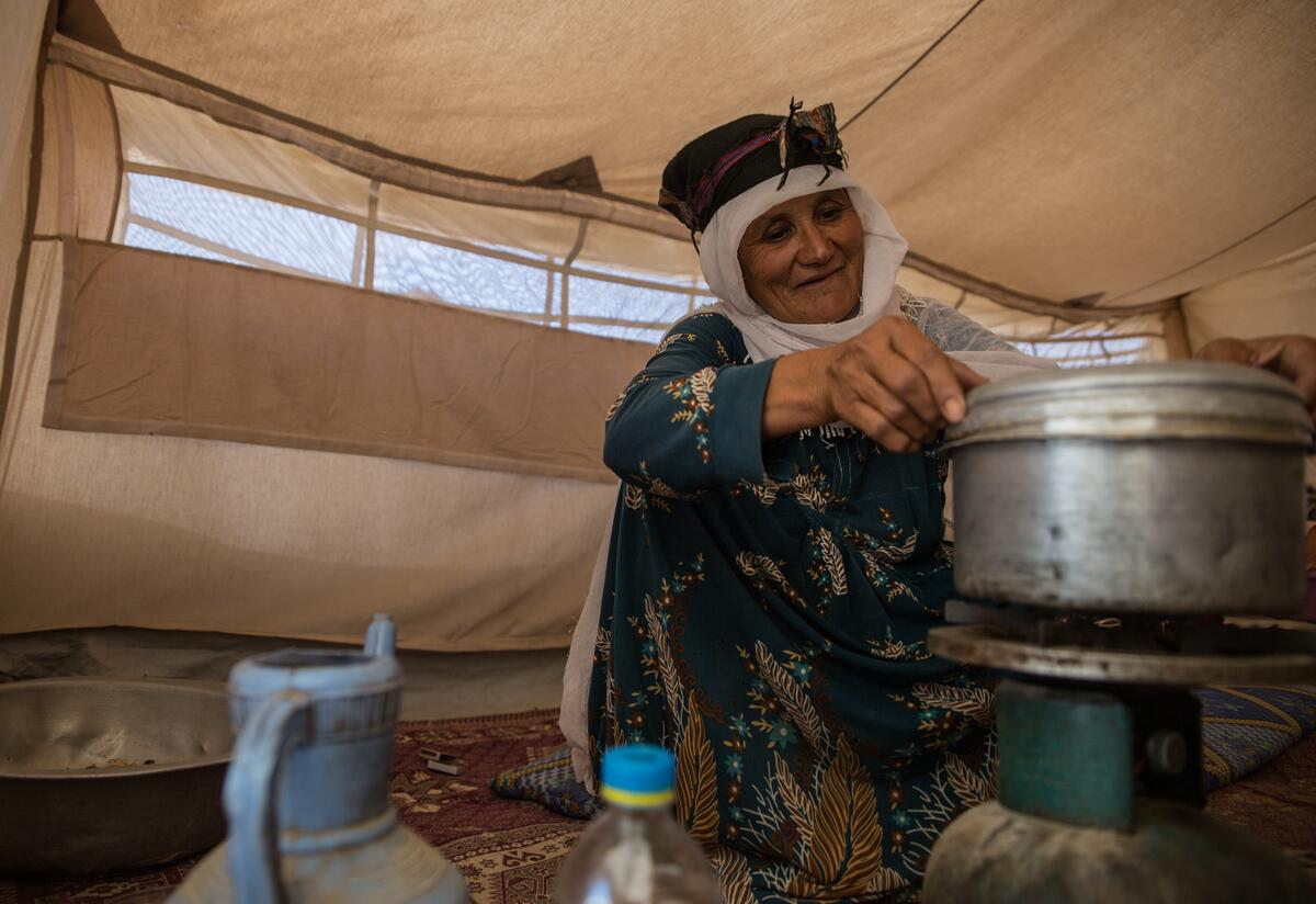 An elderly Afghan woman crouches on the floor of a tent in a camp in Badghis, Afghanistan cooking a meal in an aluminum pot on a burner.