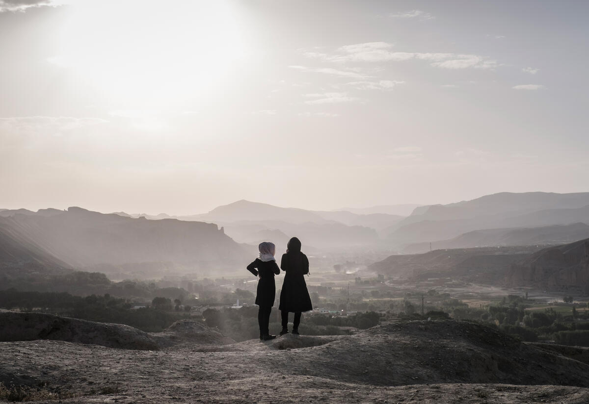A landscape photo with a mountainous landscape and the silhouettes of two girls who are looking at the landscape with their backs to the camera.