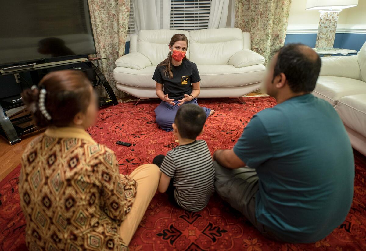 Jessica Carey, an IRC employment specialist, sits on the floor in a living room facing and talking to a family of three, parents and a young child.