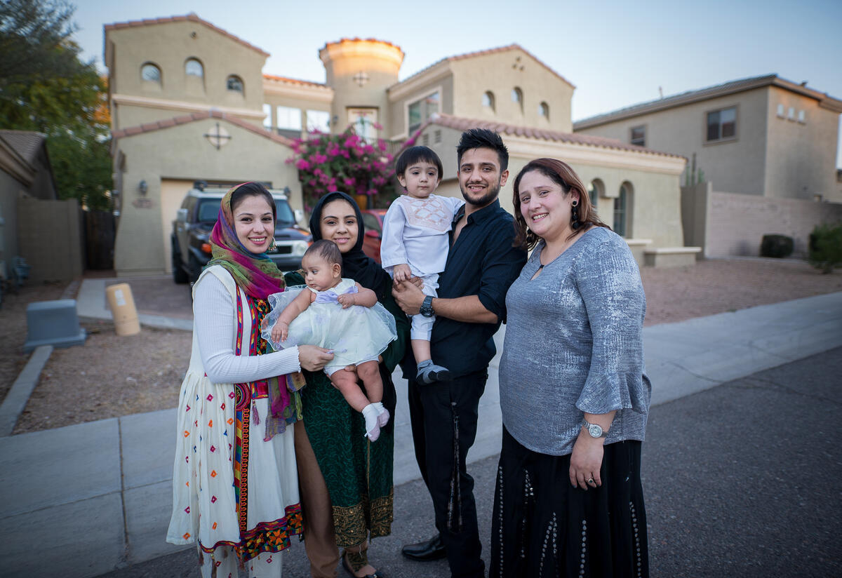 An Afghan refugee family stands outside their home in the US.
