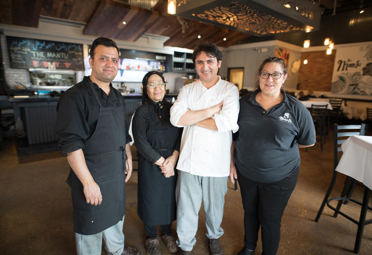 A chef stands with his staff in his restaurant.
