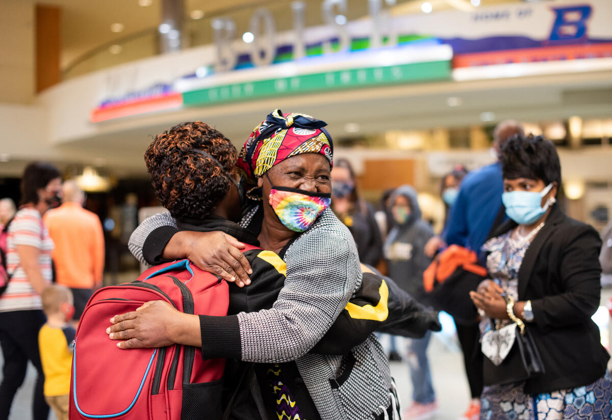 Two refugee women hug after being reunited in an airport.