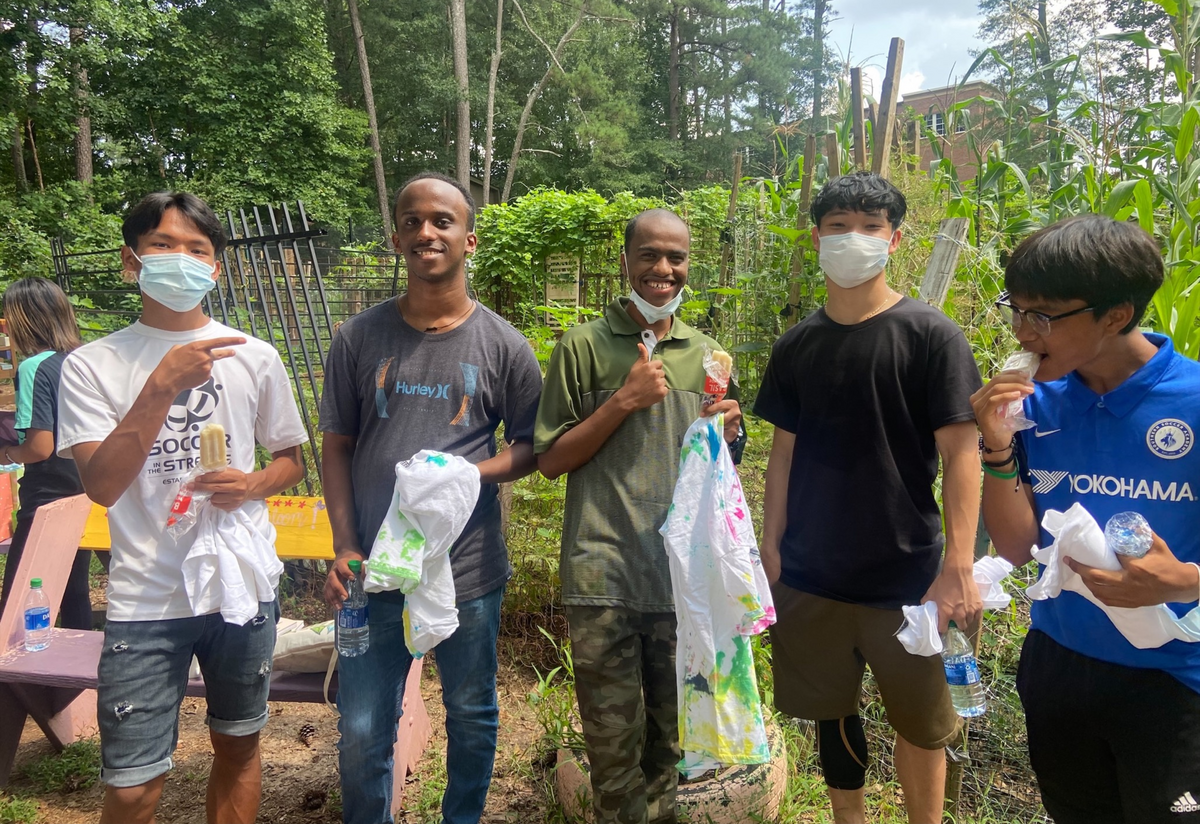 A group of 5 male high school students, 3 of Asian decent and 2 of African descent, standing in a community garden and eating popsicles.