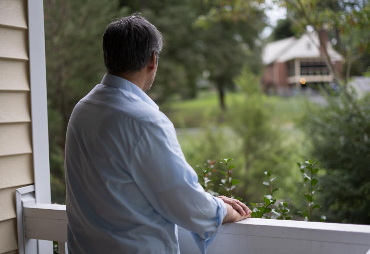 Afghan refugee Abdul, 52, stands alone on the porch of a friend's home in Virginia, looking out over the railing.