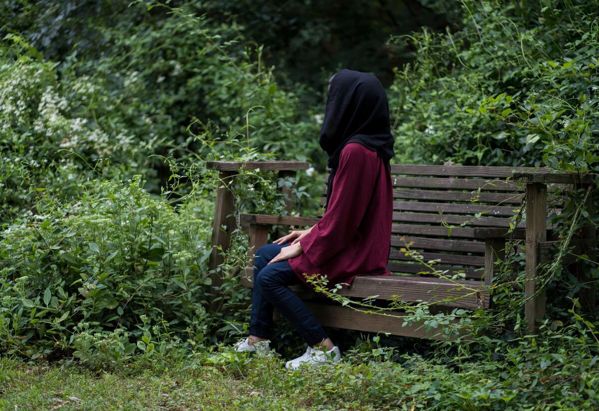 Afghan refugee Fatima, 19, sits facing sideways on a wooden garden swing in a lush garden in Richmond, VA