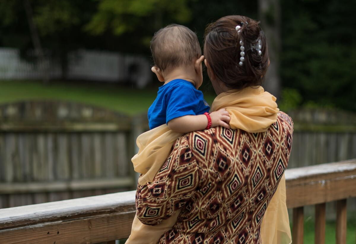 Afghan refugee Hadiya, 27, holds her yougest child as they look over a wooden fence at the home where they are staying in Virginia.