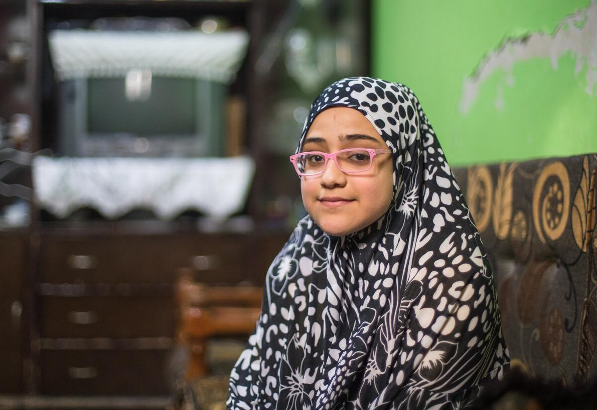 Salam, a 10-year-old Syrian girl wearing glasses, sits smiling for a photo.
