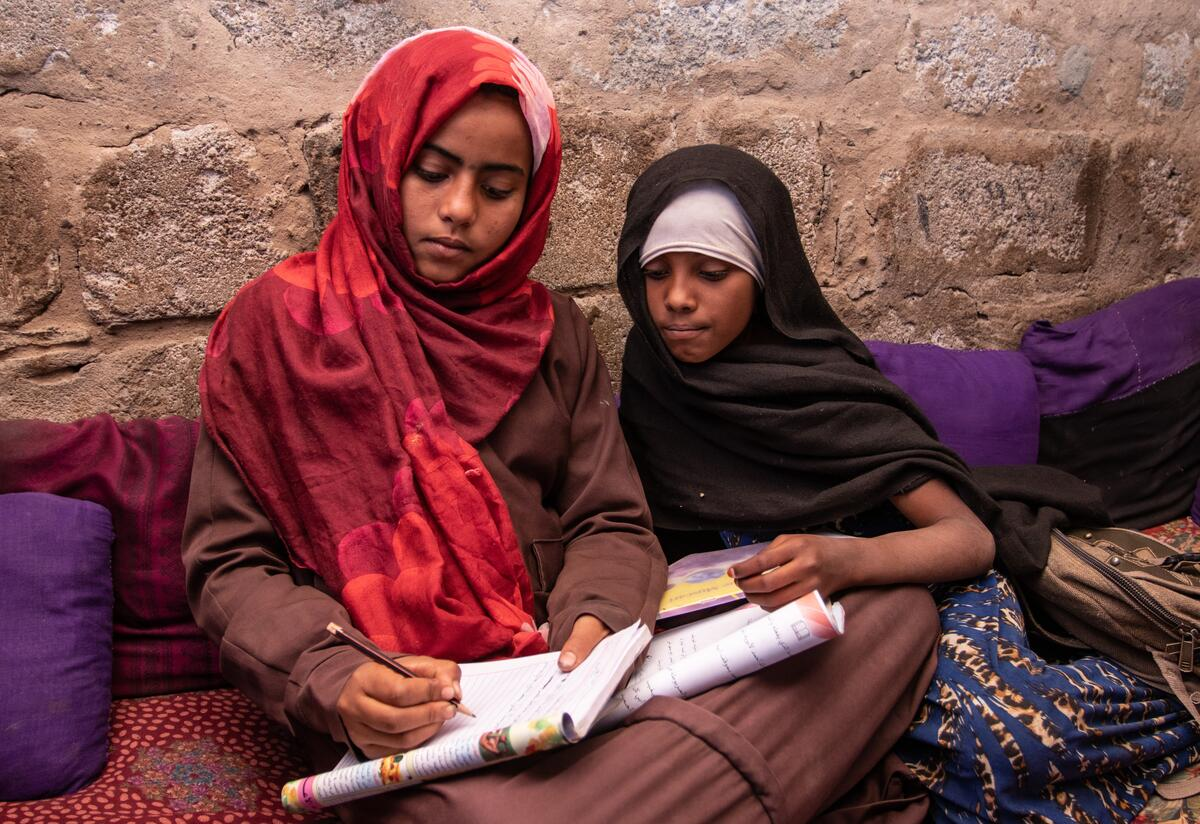 In a camp for displaced families in Yemen, Na'aem, 11 and Aisha, 10, sit on the ground going over a school workbook together and writing. The girls are best friends.