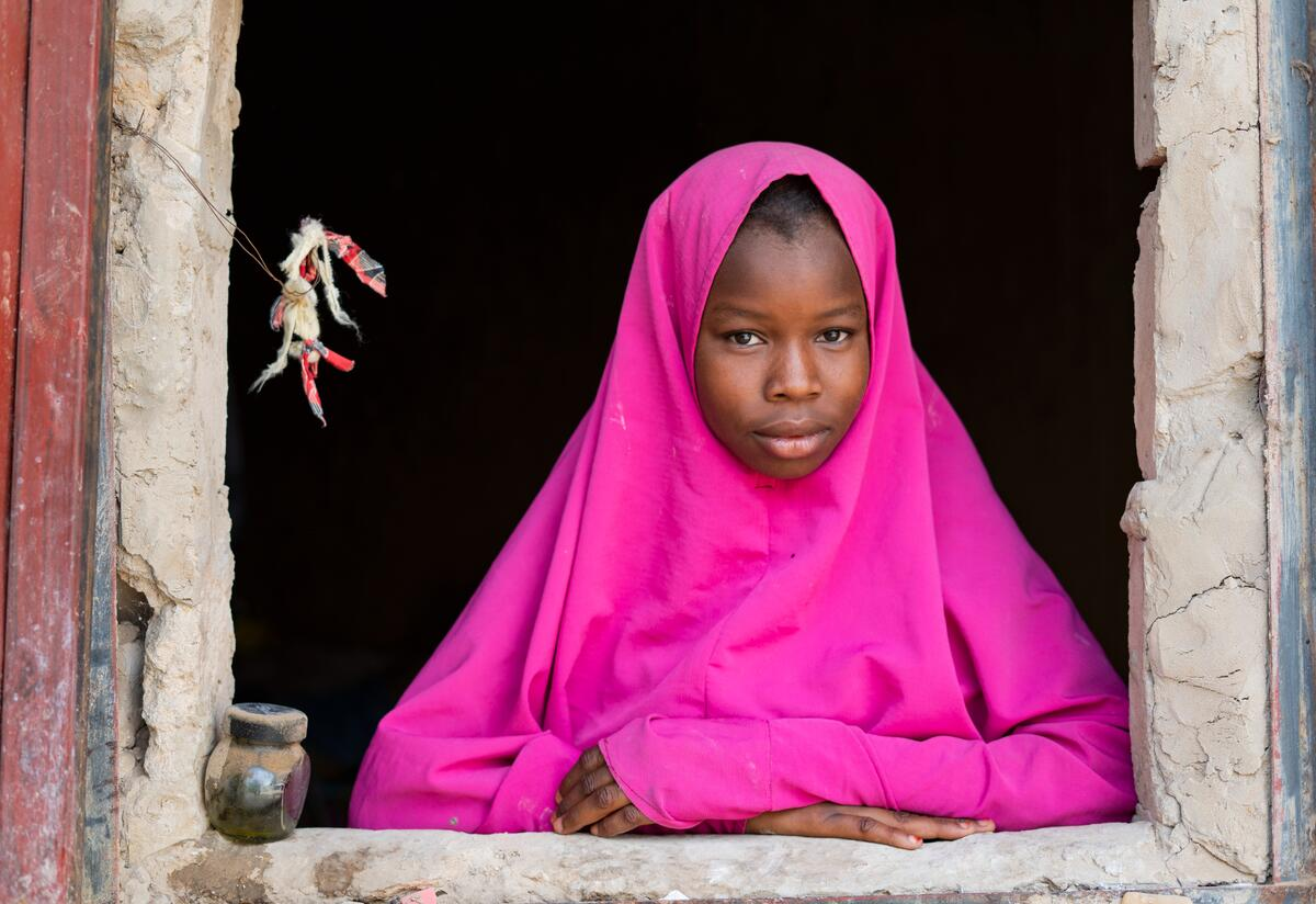 Maryama, age 15, stands framed in a window at her home in Niger.