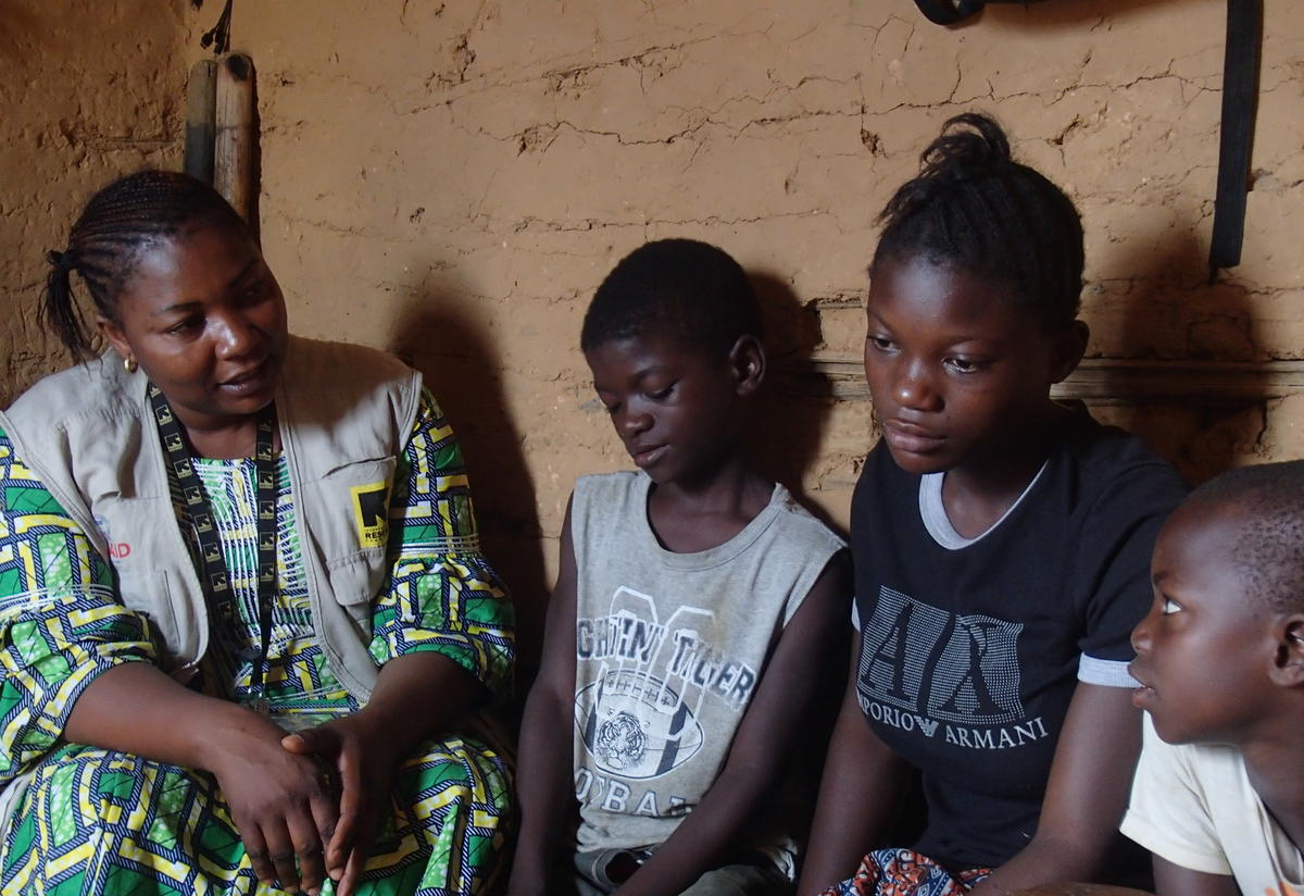 Orphans Anita, Franck, and Freddy talking with IRC worker