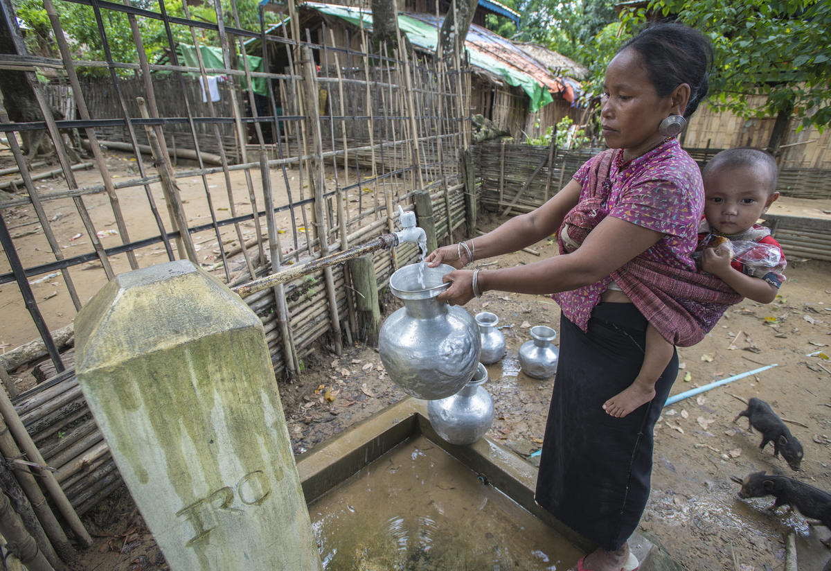 Woman in Myanmar collects water from IRC tap