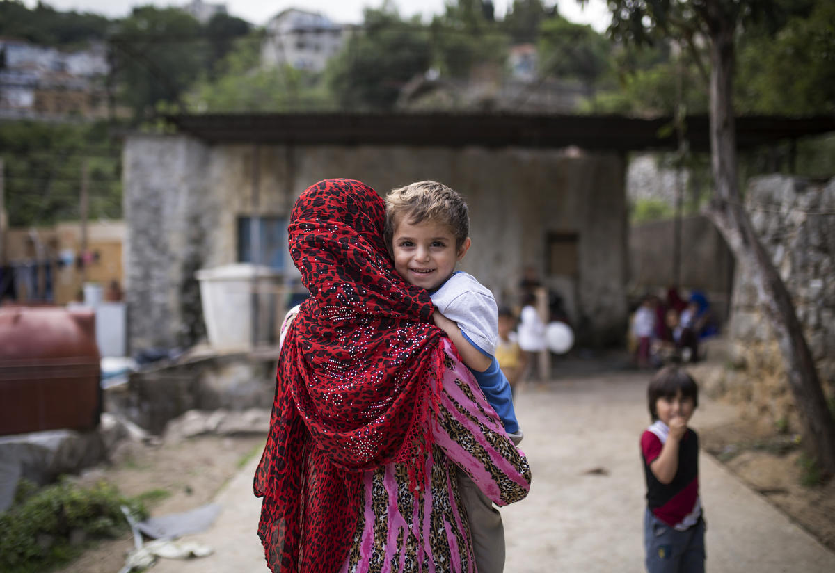 A Syrian mother in Lebanon carries her child