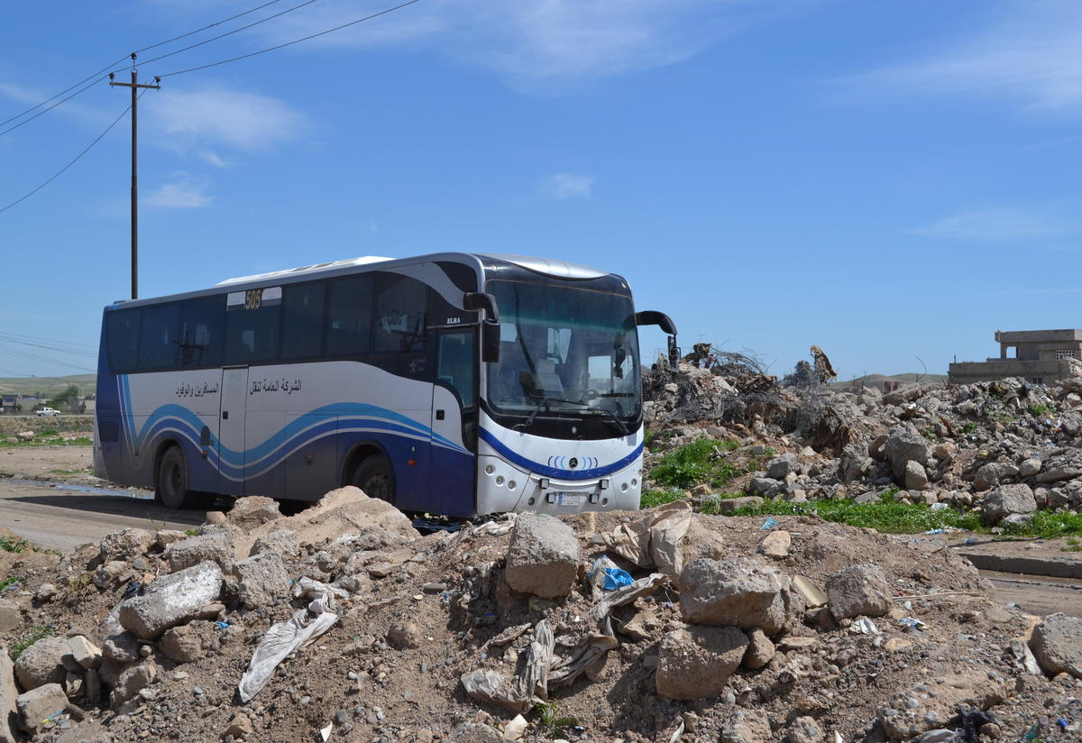 A bus carries displaced Iraqis to a screening center