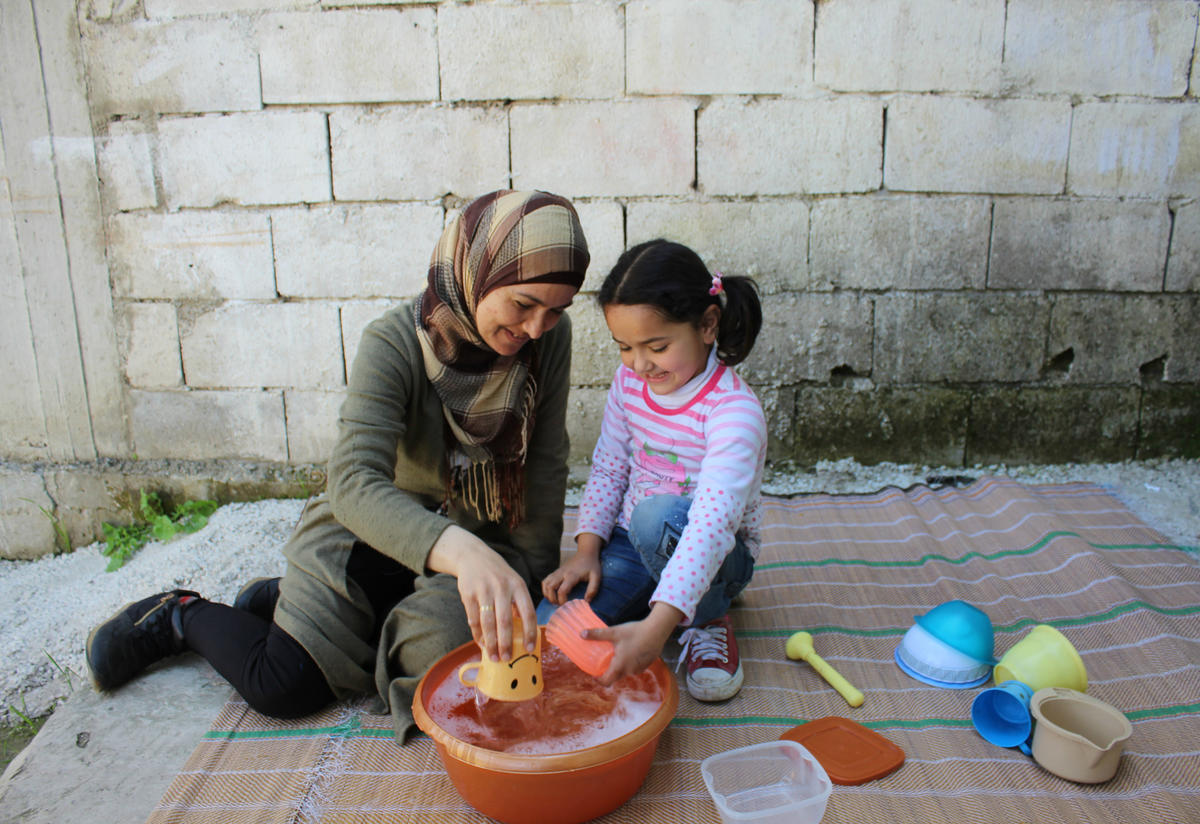Ahlam and Sadal do an activity together while washing dishes