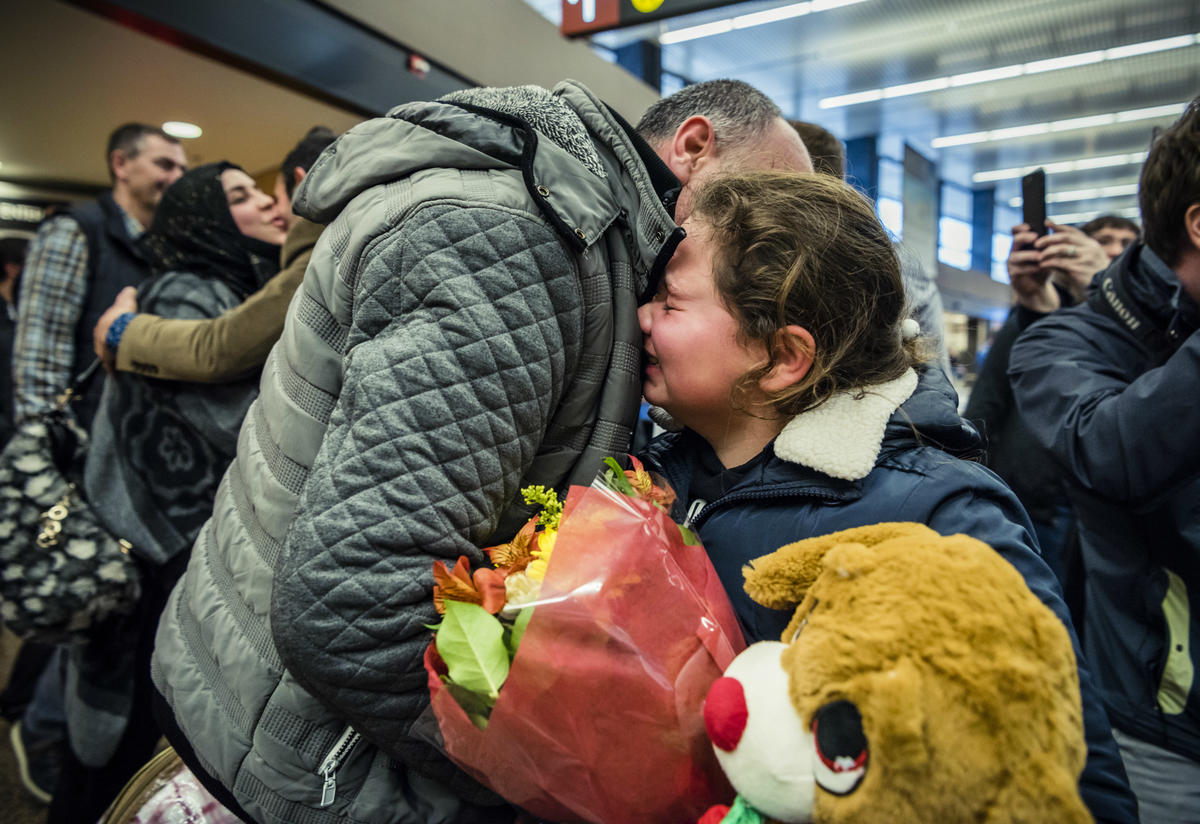 Syrian father and daughter embrace at a Seattle airport as their family is reunited