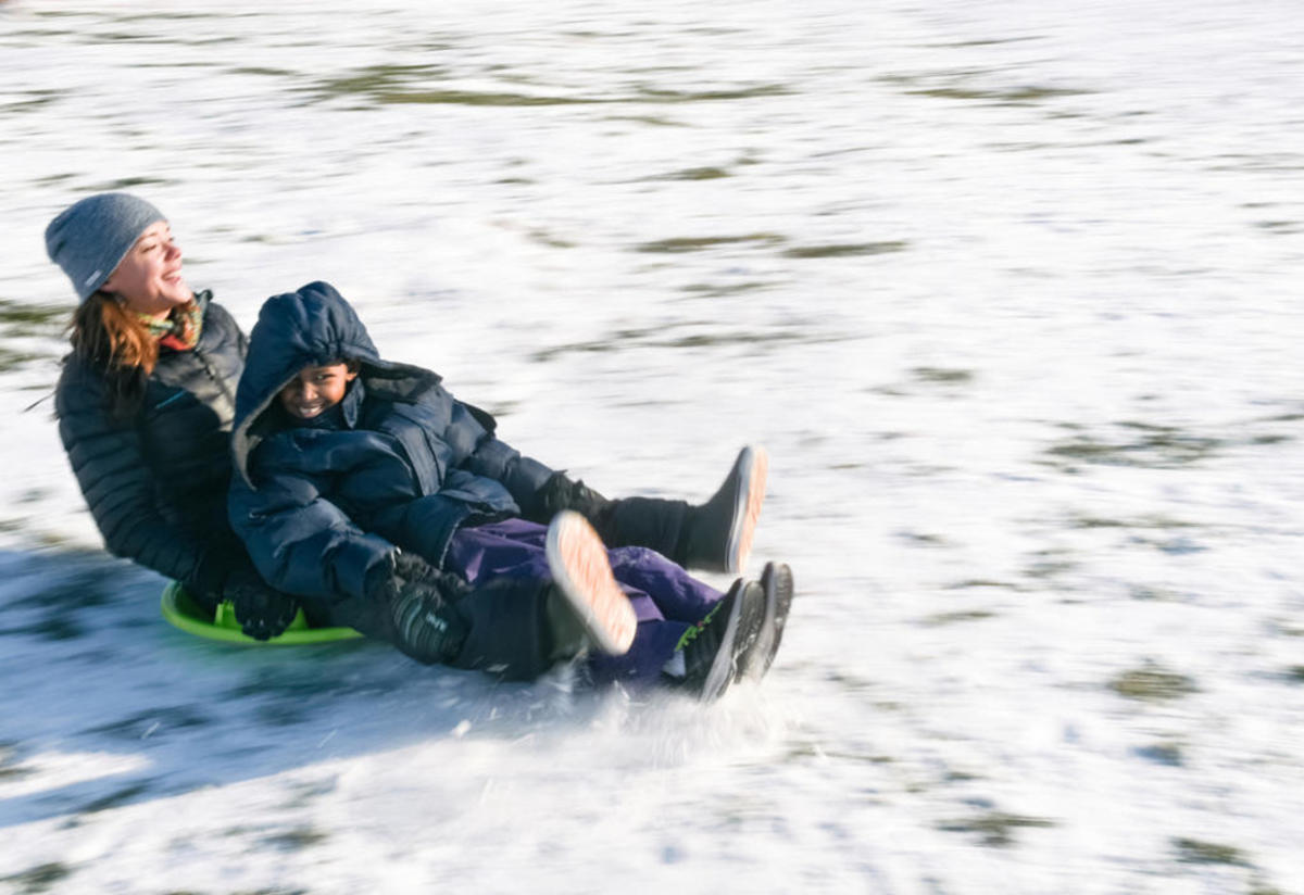 Jamie Utz and eight-year-old Muhammed Samatar sled down a hill in Boise