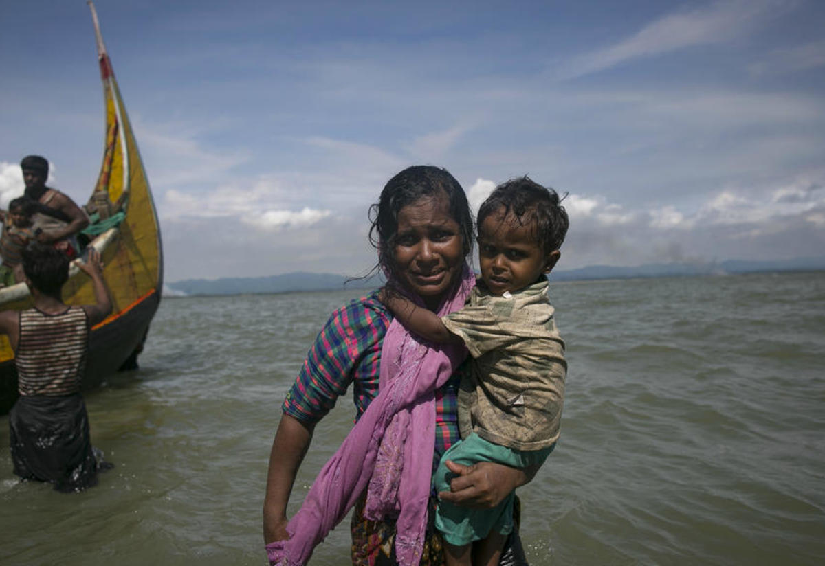 A Rohingya woman carries her child to shore in Bangladesh after fleeing violence in Myanmar's Rakhine State by boat.