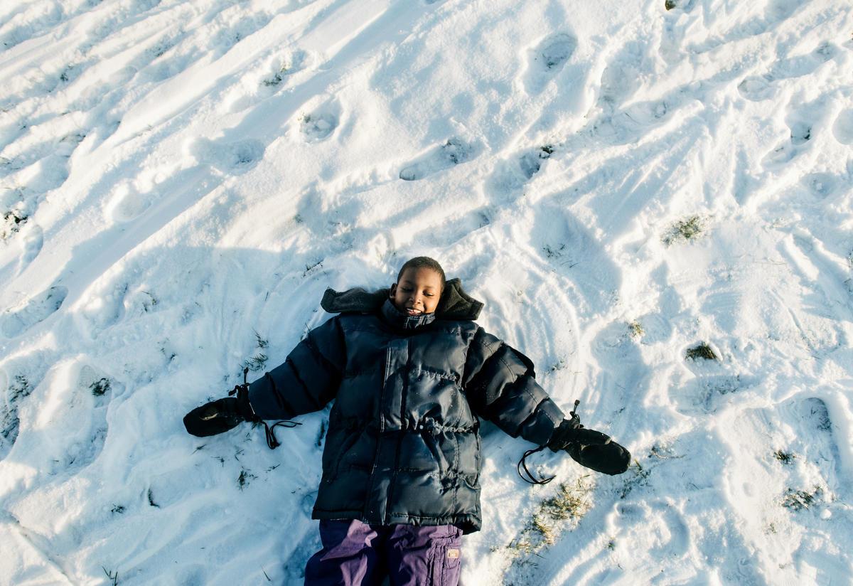 An 8-year-old SOmali boy makes a snow angel.