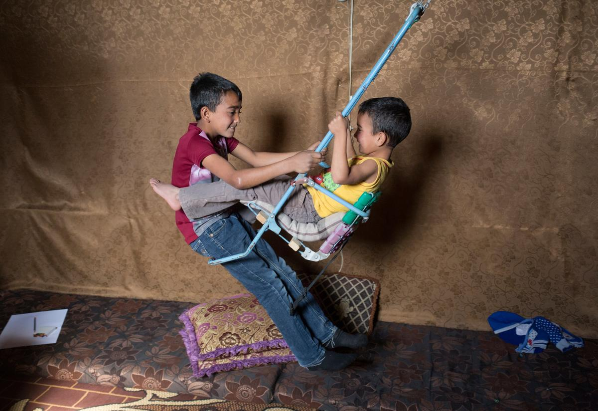 Two Syrian boys play on a homemade swing in their tent