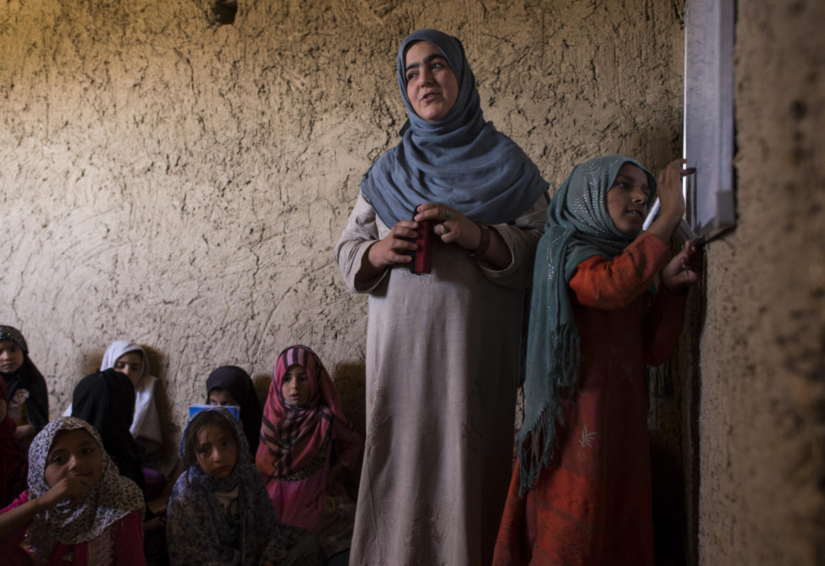 A teacher leads her class in Afghanistan as a girl writes on the board