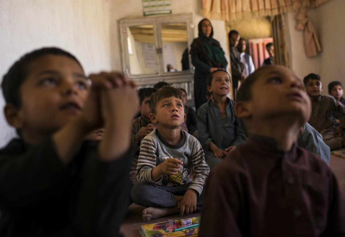Boys sitting on the floor listen to their teacher in Afghanistan