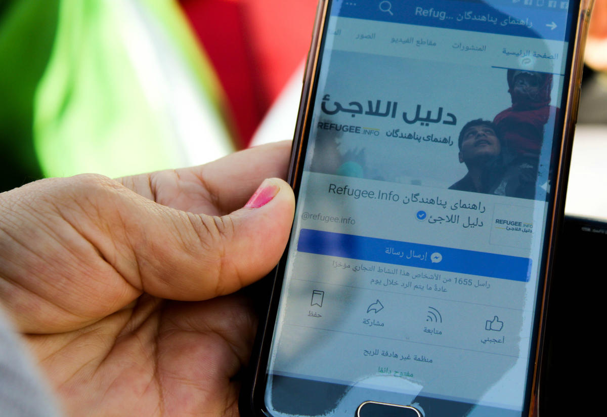 Close-up of a phone a woman is using to access Refugee.Info