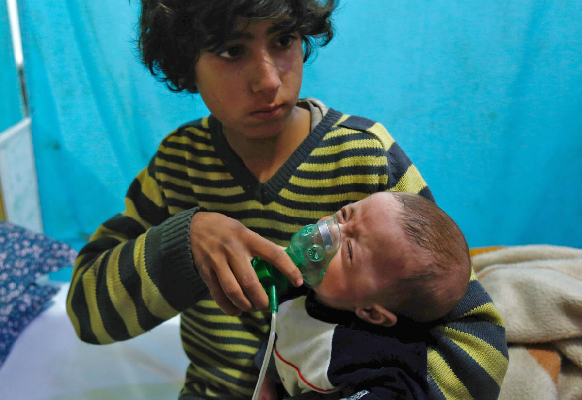 A Syrian boy holds an oxygen mask over the face of an infant at a make-shift hospital