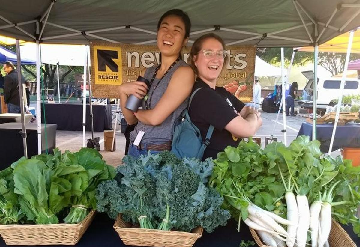 Yui Iwase and a volunteer at the farmers market with New Roots