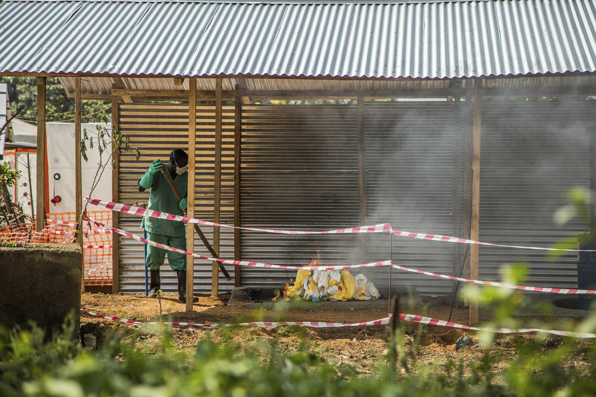 A health worker at Beni Hospital burns personal protective equipment outside the Ebola treatment center.