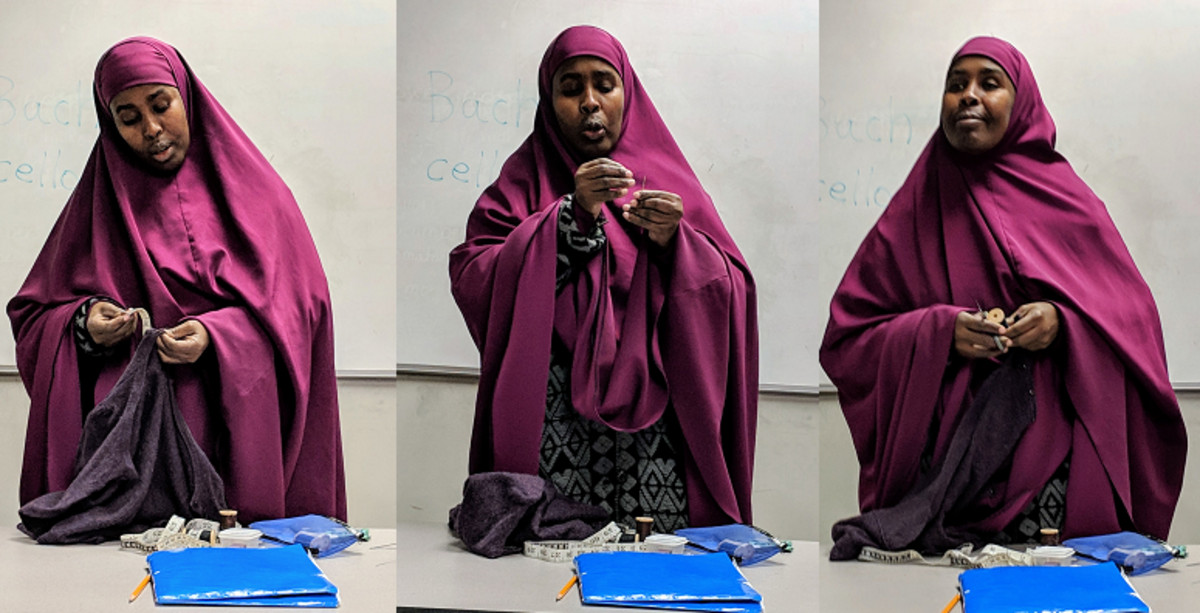 Student Hawo demonstrates how to mend torn clothing.
