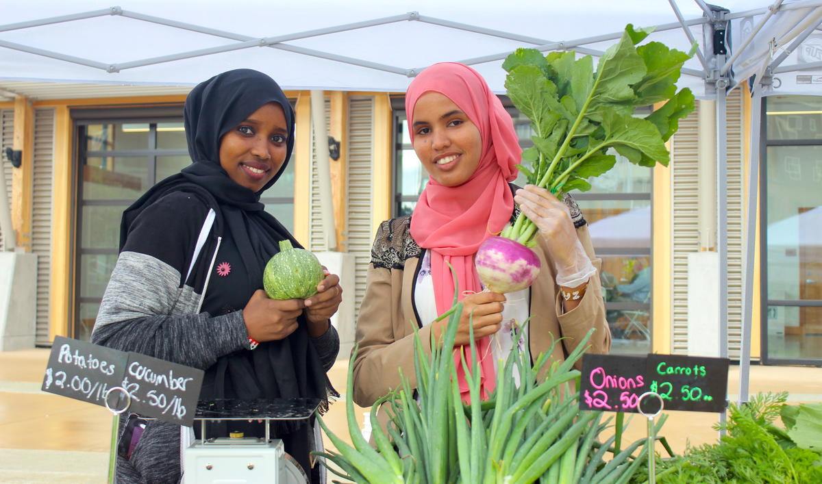 Two Youth Roots summer interns helping out at Namaste Farm Stand in Tukwila