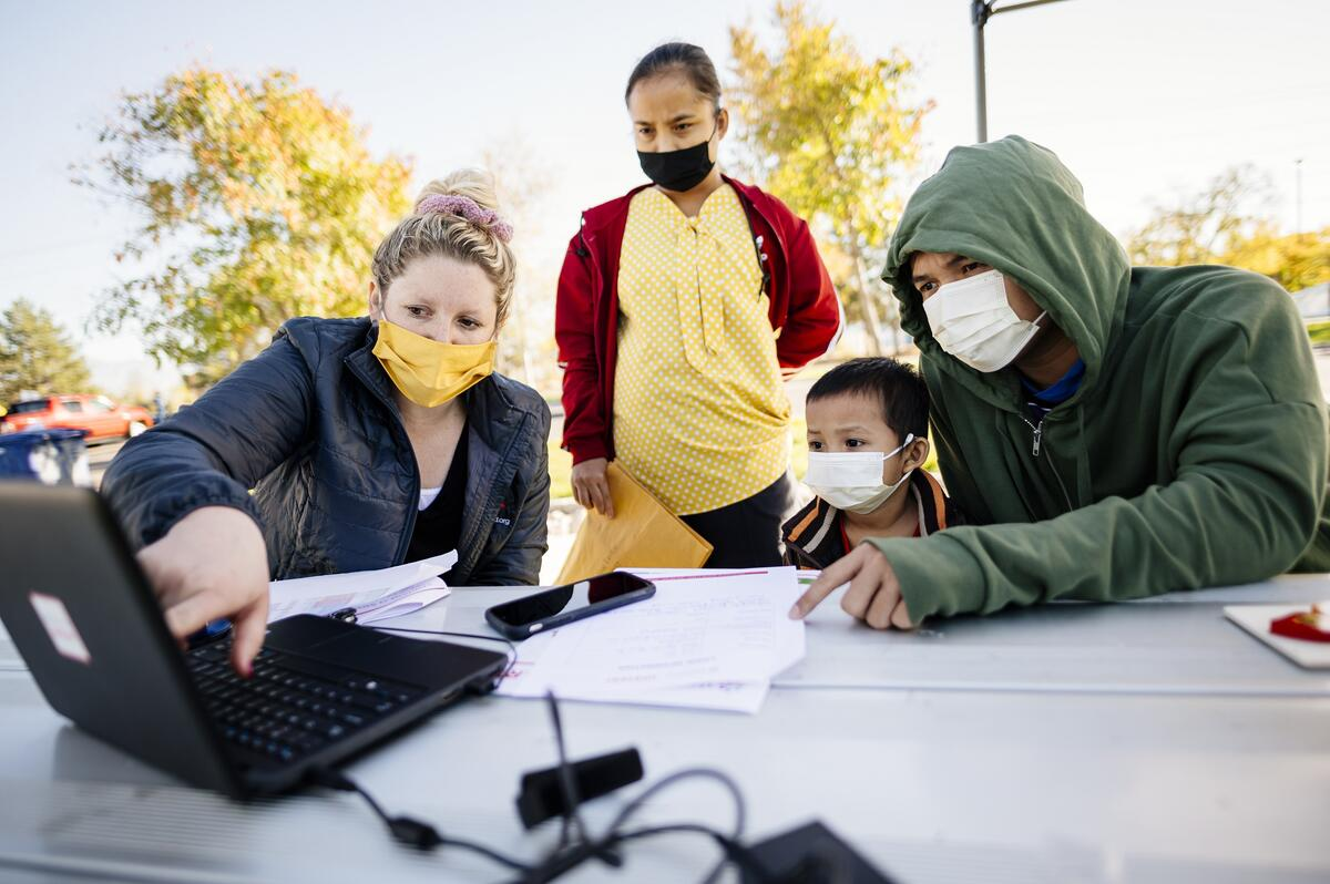 A family gathers with an educator outdoors around a laptop to complete activities for their students, all wear masks.
