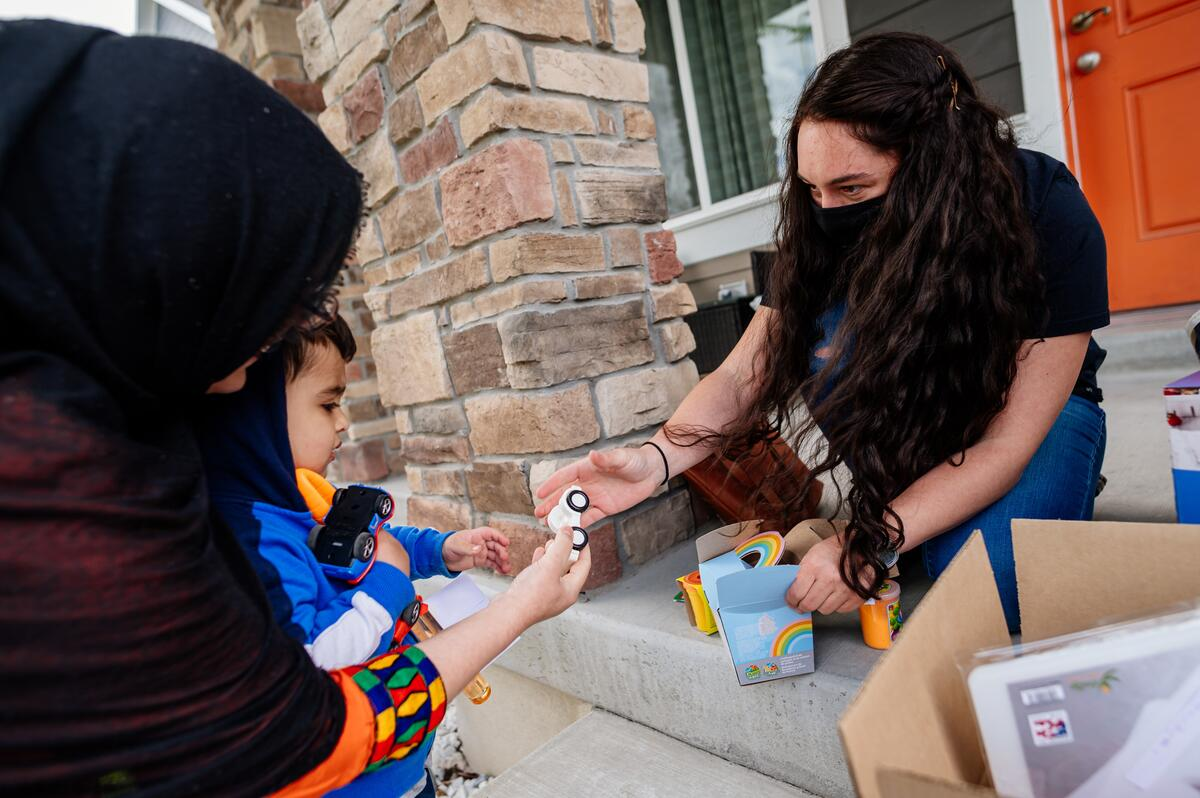 A woman kneels at the top of two steps, reaching out to hand a boy in his mother's arms a toy car provided by volunteers of the International Rescue Committee in Salt Lake City.