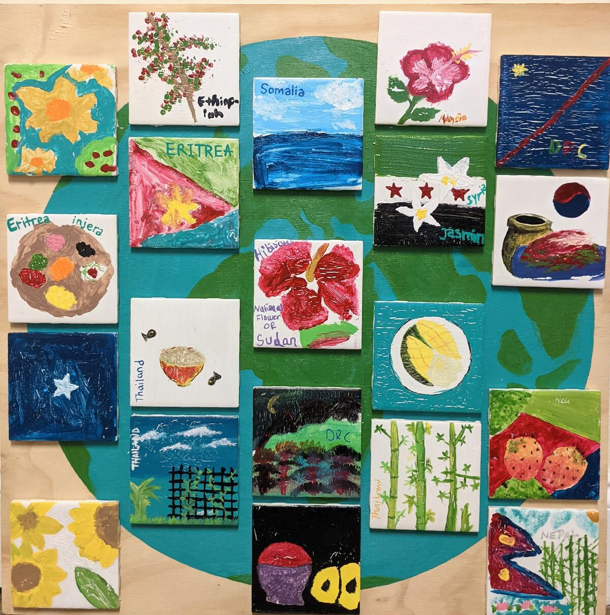 A collection of paintings by students. The images include various kinds of flowers, vines, and fruit and all the canvases are on top of a painting of the globe.