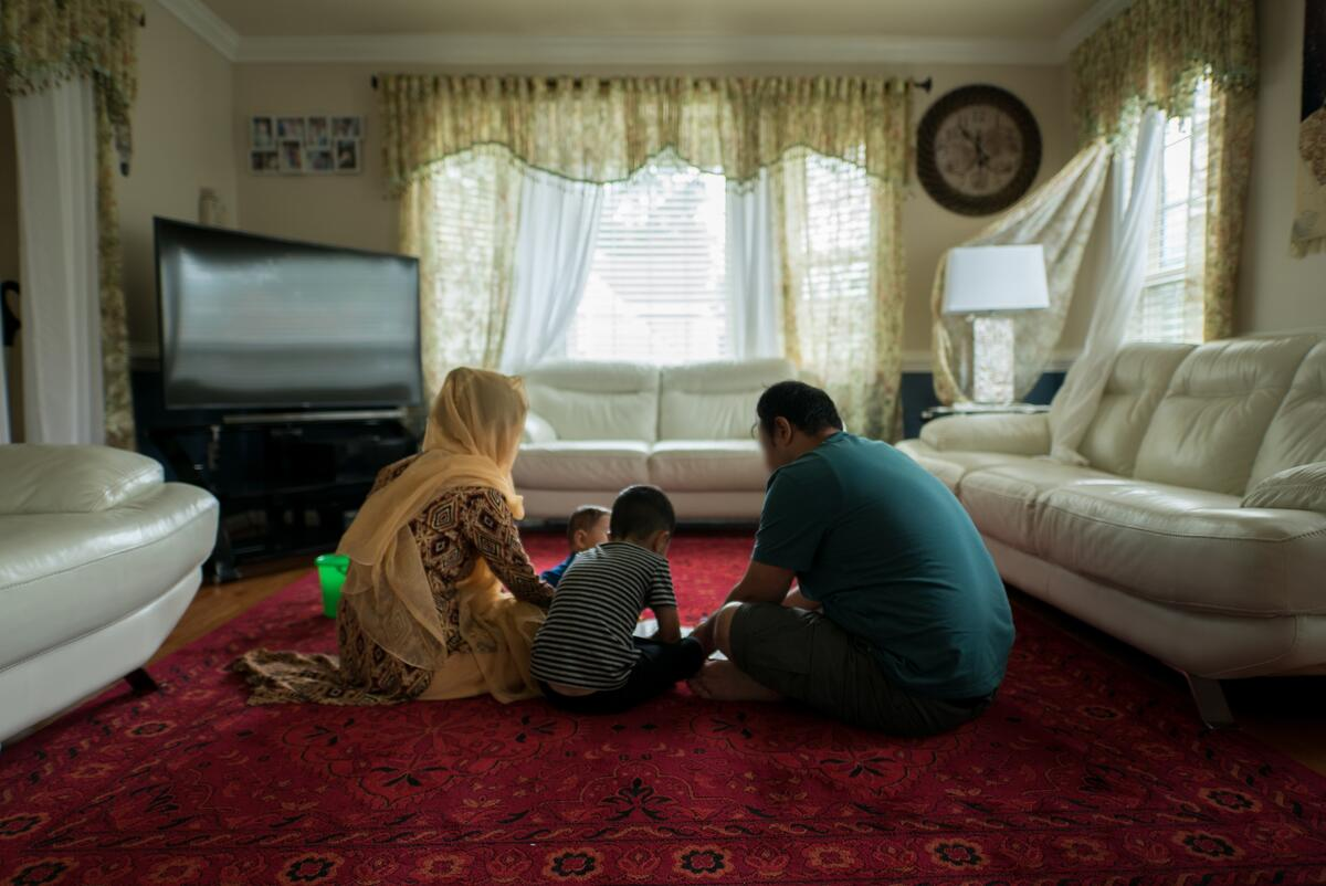 Afghan refugees Hadiya and Ali play with their two young children on the living room carpet of a friend's home in Virginia