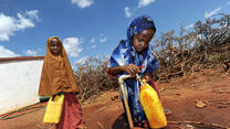 Two girls fill water jugs at an IRC-installed tap in Galkayo, Somalia