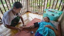 An IRC health worker takes the blood pressure of a female patient lying on a mat on the floor in Thailand.