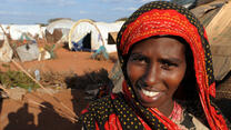 A smiling young woman stands outside a tent in Dadaab refugee camp in Kenya on a sunny day,