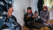 An IRC staff member talks with a Syrian refugee family seated on cushions in their shelter in Zaatari refugee camp in Jordan.